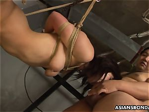 roped up to a cable and deep-throating on the fellas